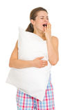 Happy young woman in pajamas with pillow yawing Stock Photo