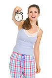 Happy young woman in pajamas showing alarm clock Royalty Free Stock Photos
