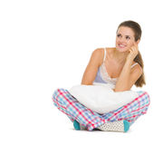 Happy young woman in pajamas sitting with pillow Royalty Free Stock Image