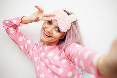 Happy young woman in pajamas and sleep mask. Woke up in the morning. Charge of vivacity royalty free stock photo