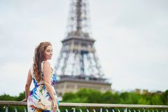 Happy young woman in Paris, near the Eiffel tower Royalty Free Stock Image