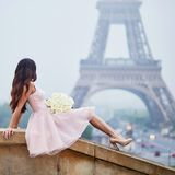 Happy young woman in Paris, near the Eiffel tower Stock Photos