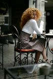 Happy young woman in a Paris style street cafe Royalty Free Stock Images