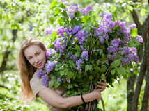 Happy young woman in park with a big bouquet of a lilac Royalty Free Stock Image