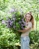 Happy young woman in park with a big bouquet of lilac Stock Photography