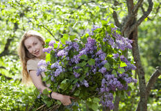 Happy young woman in park with a big bouquet of a lilac Stock Photos