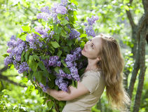 Happy young woman in park with a big bouquet of a lilac Royalty Free Stock Photography