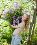 Happy young woman in park with a big bouquet of a lilac. Royalty Free Stock Photography