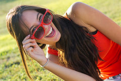 Happy young woman at the park. Portrait of happy young woman at the park whit sunglasses Royalty Free Stock Photo