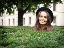 Happy young woman in a park. Happy smiling young woman in a park looking over hedge Royalty Free Stock Photos