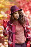 Happy young woman in park on sunny autumn day. Cheerful beautifu Stock Image