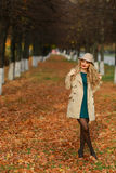 Happy young woman in park on sunny autumn day. Cheerful beautiful girl in coat and floppy hat outdoors on beautiful fall day. Royalty Free Stock Images