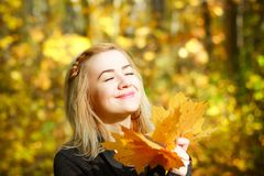 Happy young woman in park on sunny autumn day. Cheerful beautiful girl in gray sweater outdoors on beautiful fall day. royalty free stock photography