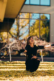 Happy young woman in park on sunny autumn day, laughing, playing leaves. Cheerful beautiful girl in black retro dress autumn fashi Stock Photo
