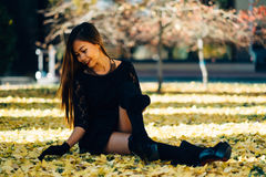 Happy young woman in park on sunny autumn day, laughing, playing leaves. Cheerful beautiful girl in black retro dress autumn fashi Royalty Free Stock Photo