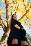 Happy young woman in park on sunny autumn day, laughing, playing leaves. Cheerful beautiful girl in black retro dress autumn fashi Stock Photography