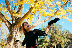 Happy young woman in park on sunny autumn day, laughing, playing leaves. Cheerful beautiful girl in black retro dress autumn fashi Royalty Free Stock Photography