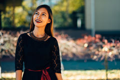 Happy young woman in park on sunny autumn day, laughing, playing leaves. Cheerful beautiful girl in black retro dress autumn fashi Stock Images
