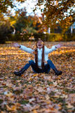 Happy young woman in park on sunny autumn day, laughing, playing leaves. Cheerful beautiful girl in white sweater during autumn se Stock Image