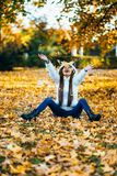 Happy young woman in park on sunny autumn day, laughing, playing leaves. Cheerful beautiful girl in white sweater during autumn se. Ason in the park stock images