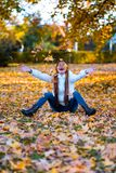 Happy young woman in park on sunny autumn day, laughing, playing leaves. Cheerful beautiful girl in white sweater during autumn se. Ason in the park royalty free stock photography