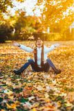 Happy young woman in park on sunny autumn day, laughing, playing leaves. Cheerful beautiful girl in white sweater during autumn se Stock Photo