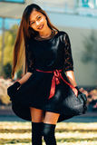 Happy young woman in park on sunny autumn day, smiling. Cheerful beautiful girl in black retro dress autumn fashion style Stock Images