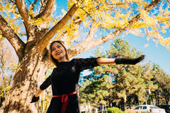 Happy young woman in park on sunny autumn day, smiling. Cheerful beautiful girl in black retro dress autumn fashion style Stock Photo