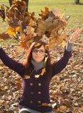 Happy young woman in the park. Happy young woman throwing autumn fallen leaves in the air royalty free stock photography