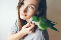 Happy young woman with parrot sitting on her shoulder. Stock Photo