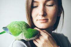 Happy young woman with parrot sitting on her shoulder. Royalty Free Stock Photos