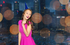 Happy young woman in party cap over night city Stock Images