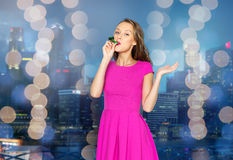 Happy young woman with party horn over night city Royalty Free Stock Image