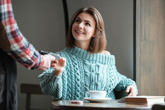 Happy young woman pays for her order with debit card. Royalty Free Stock Image