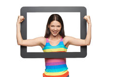 Happy young woman peeping out of tablet frame Stock Photography