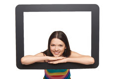 Happy young woman peeping out of tablet frame Royalty Free Stock Photos
