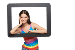 Happy young woman peeping out of tablet frame Stock Images