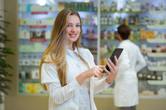 Happy young woman pharmacist over drugstore background. Happy young women pharmacist over drugstore background, holding digital tablet, in the background is a Stock Photos