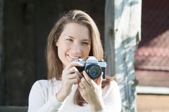 Happy young woman photographer using old camera Royalty Free Stock Images