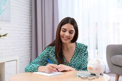 Happy young woman with piggy bank and money royalty free stock photo