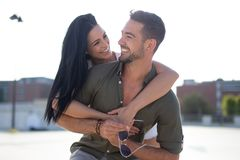 Happy young woman piggyback ride man outdoors in sunset stock photography