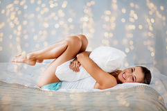 Happy young woman with pillow lying in bed at home. Rest, sleeping, comfort and people concept - happy young woman with pillow lying in bed at home bedroom Stock Image