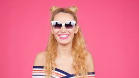 Young woman on a pink background with sunglasses. Happy Young woman on a pink background with sunglasses stock video footage
