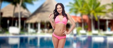 Happy young woman in pink bikini swimsuit on beach Stock Photography