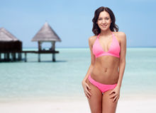 Happy young woman in pink bikini swimsuit on beach Royalty Free Stock Image