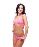Happy young woman in pink bikini swimsuit Stock Image