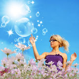 Happy young woman in pink dreams. Upon green summer solar flowers meadow Royalty Free Stock Image