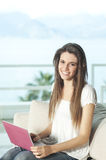Happy young woman with pink netbook Royalty Free Stock Images