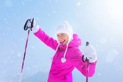 Happy young woman in pink ski jacket holding ski poles in gloves royalty free stock images