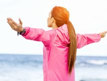 Young woman in sportswear standing at the seaside. Happy young woman in pink sportswear standing at the seaside Royalty Free Stock Image